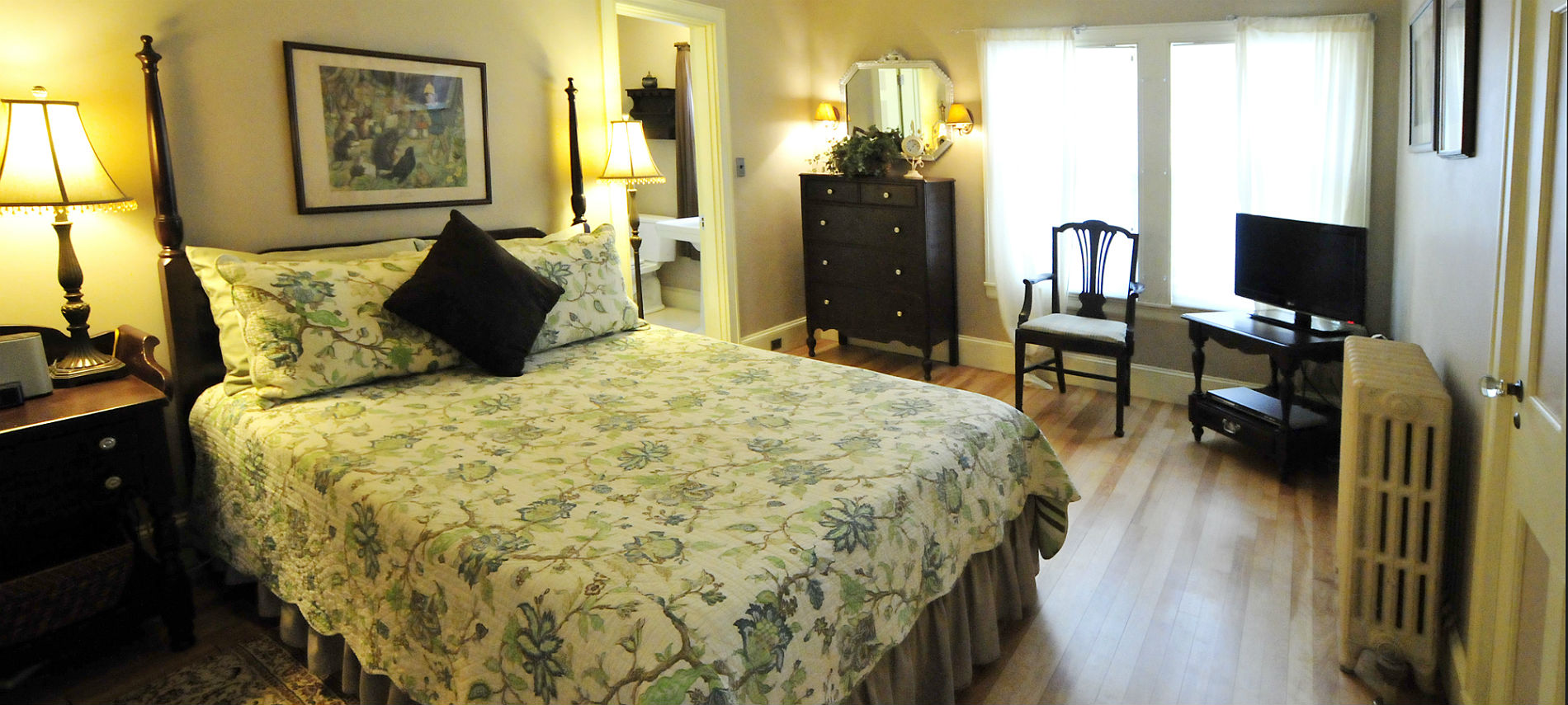 Bedroom with wood floors and dark wooden furniture featuring a large bed with a blue floral quilt.