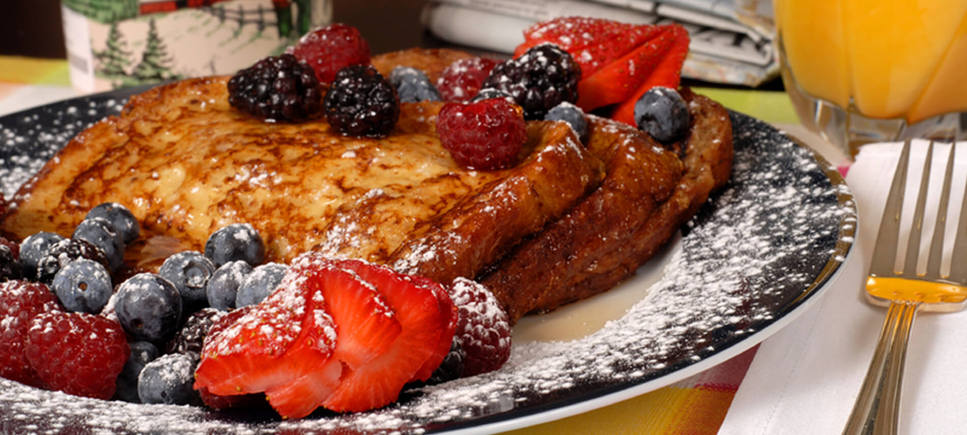 French toast with strawberries on a blue plate with orange juice.