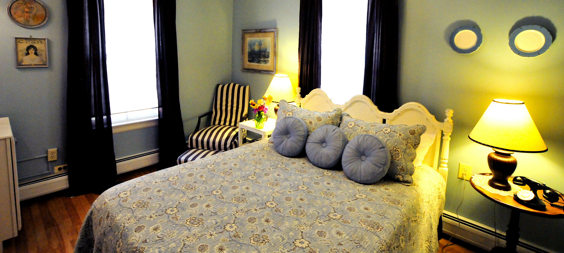 Cozy guestroom with a bed covered in a flower-print comforter and sidetables with lamps.