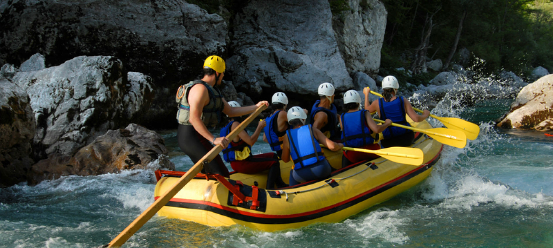 A yellow raft full of helmeted rowers in fast-moving water near rocks.