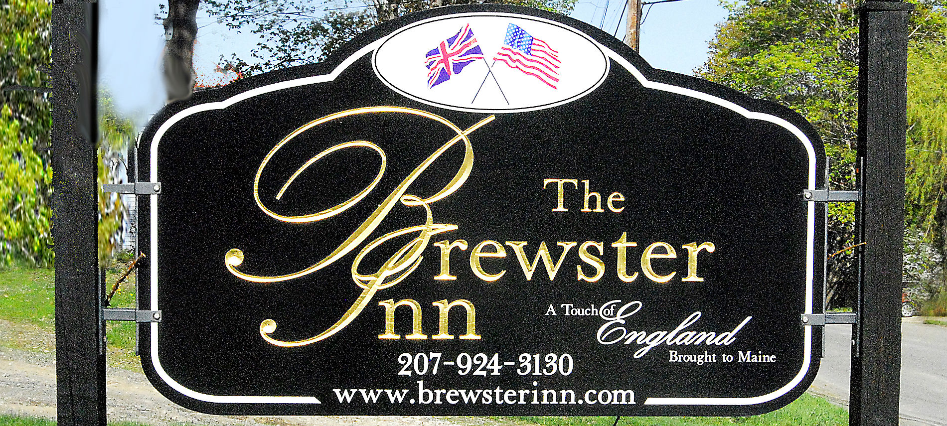 Large exterior sign in black with American and British flags crossed with text : The Brewster Inn