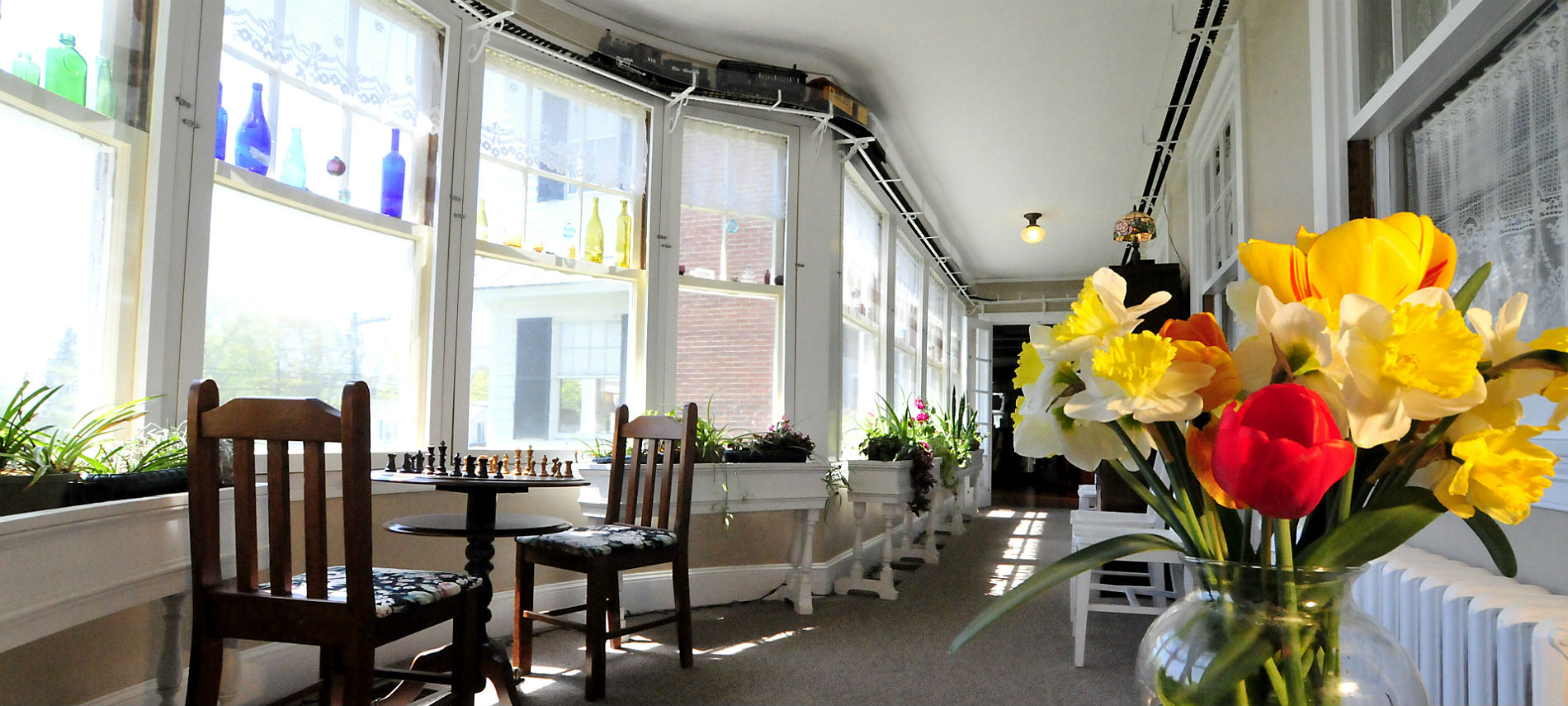 Enclosed porch with mant large windows and a small table and chairs.