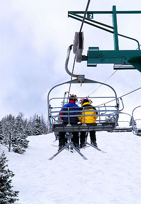 A couple in blue and yellow jackets ride a ski lift on a snowy day.
