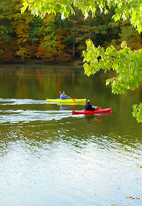 Kayakers in red and yellow kayacks paddle on clam water surrounded by autumn trees.