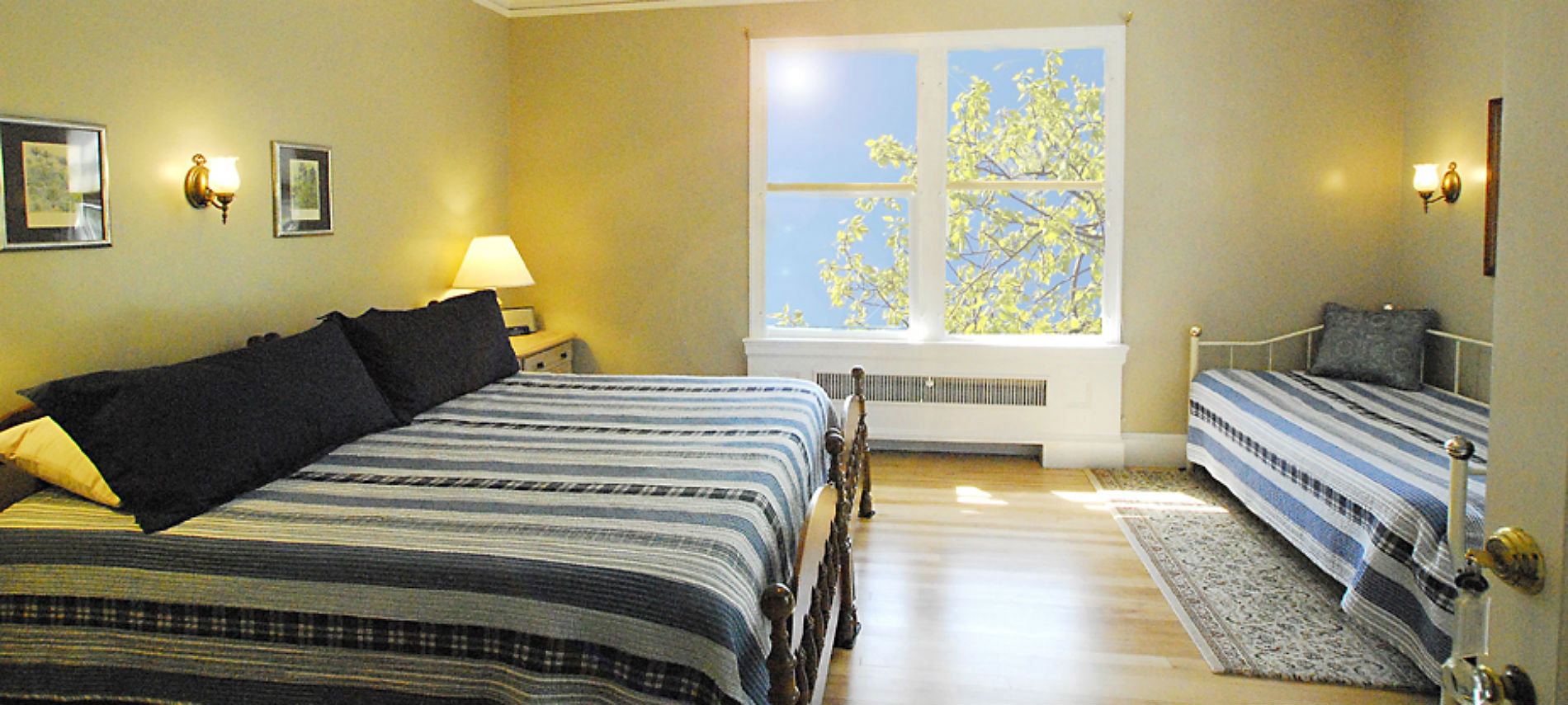 Bedroom with king sized bed and daybed covered with blue and white striped quilts.