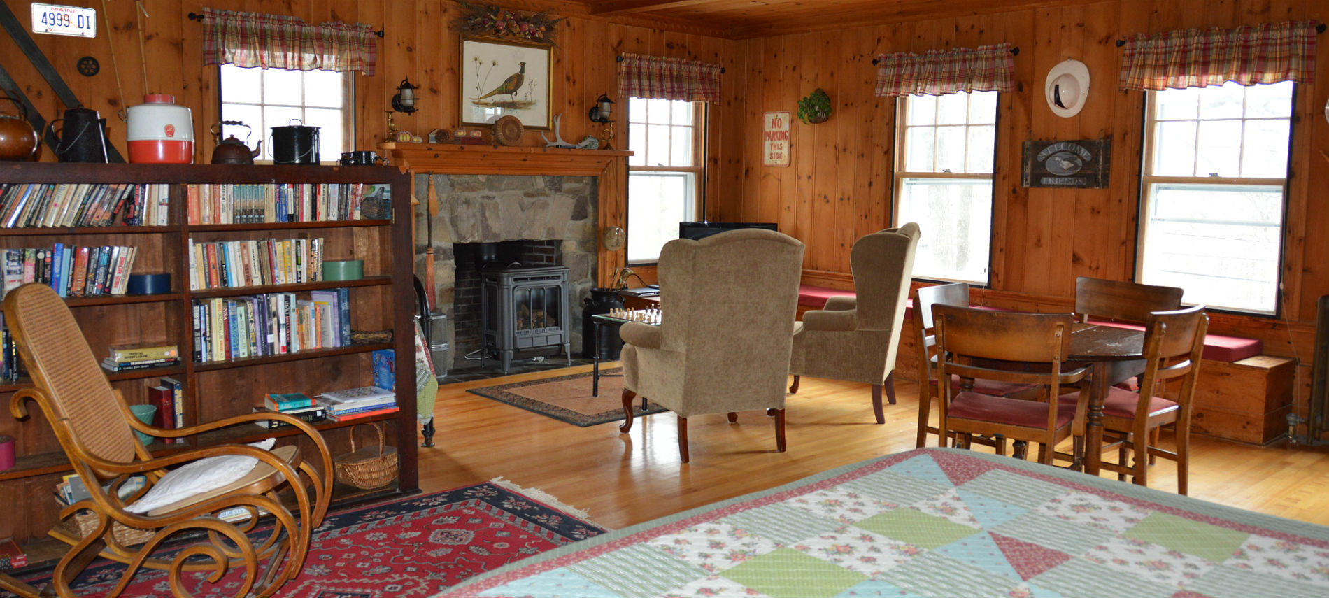 Cozy cabin-like room with a fireplace, small dining table, two wingback chairs and a bookcase.