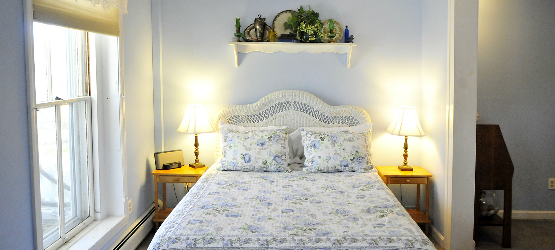 Charming wicker bed with a flowered bed cover and shams with a nightstand and lamp.