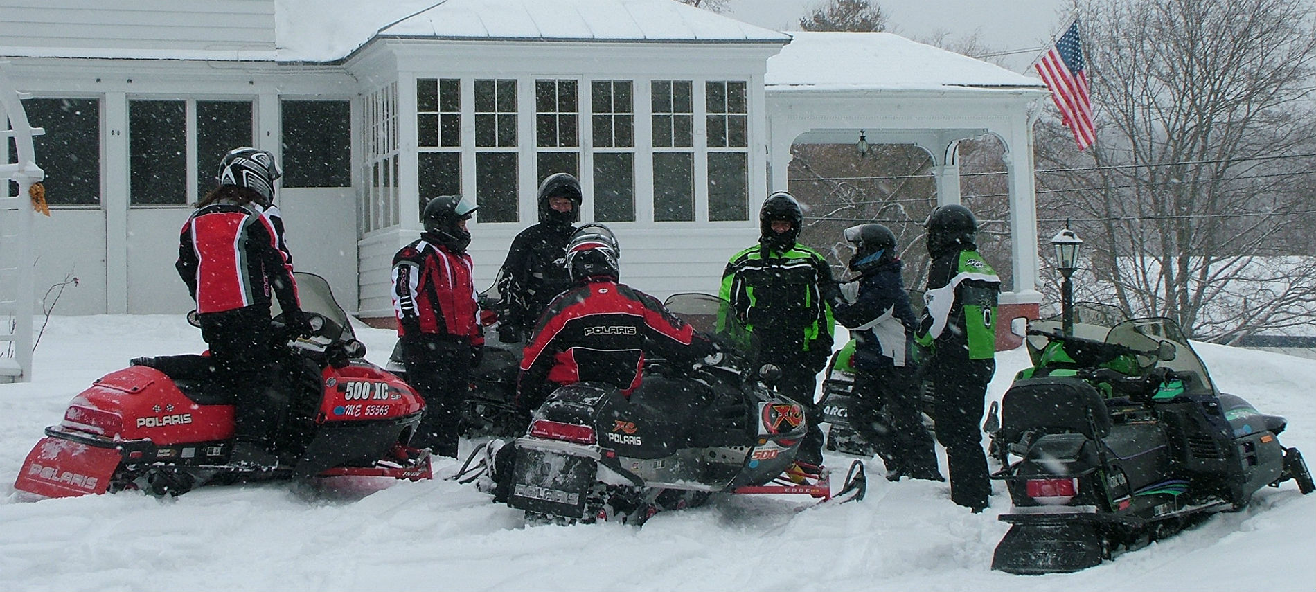 Group of snowmobilers in the snow with red and green machines and coats.
