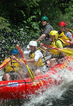 Excited people paddling a red raft through whitewater.