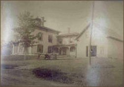 Historical ohoto of a large white house in sepia tones.