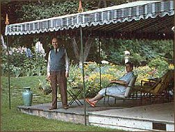 A man sits on a lawn chair and another man stands under a green and white awning.