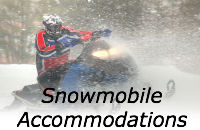 Man on a snowmobile in the snow - link to Snowmobile accommodations.