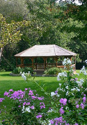 Large wooden gazebo fronted with lavender and white flowers.