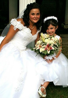 Dark haired bride and flower girl in white dresses smile at the camera.