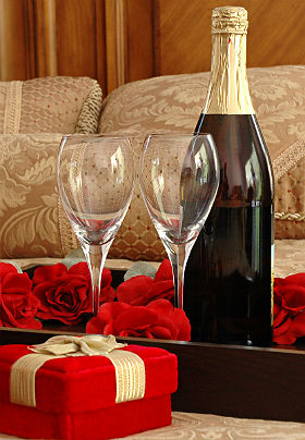 A gift wrapped in red velvet with a gold bow and a tray with champagne and glasses sit on a gold-covered bed.