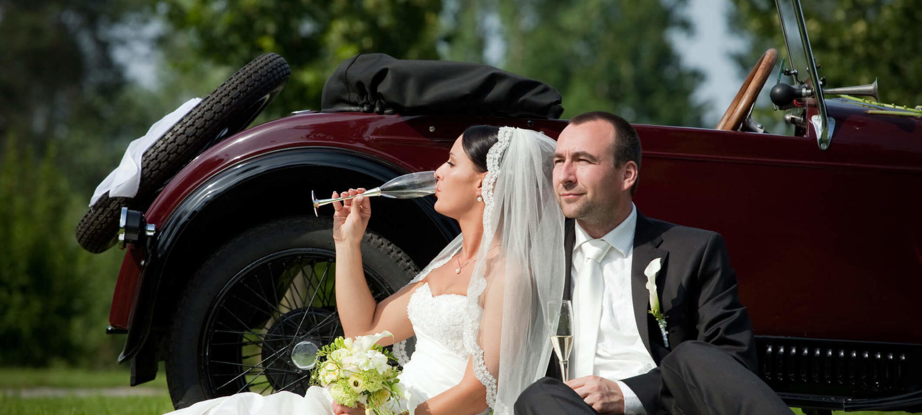 Bride and groom leaning against a classic car with glasses of champagne.